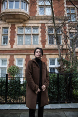 model standing in mid-length sustainable brown alpaca wool coat