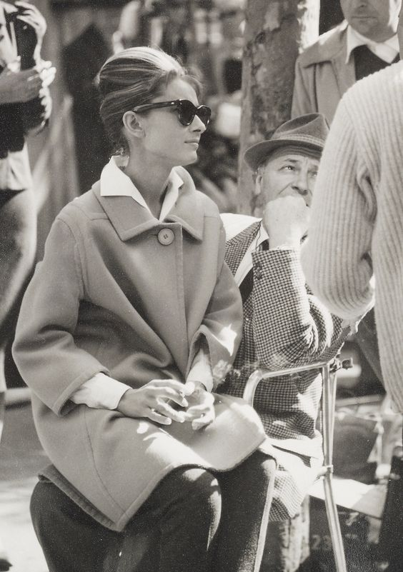 photo of actress audrey hepburn sitting with a vintage coat