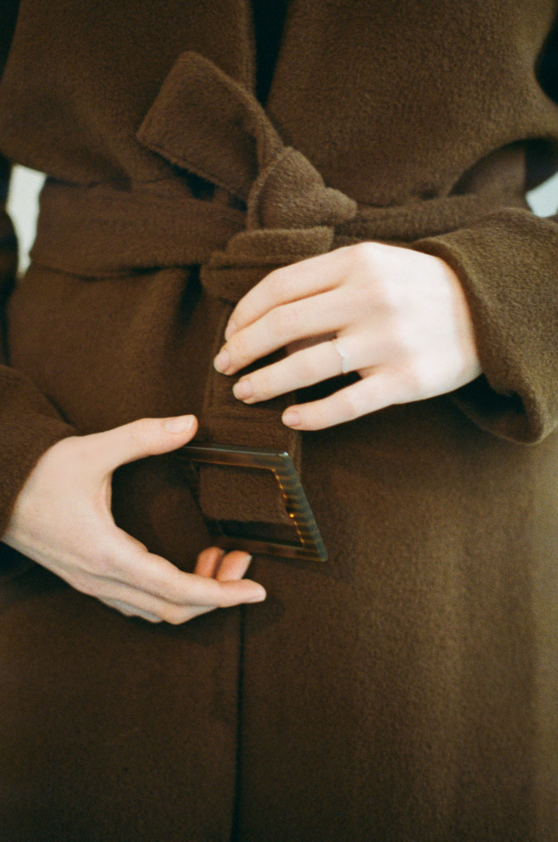 fitted brown sustainable alpaca wool coat with buckle made out of vegetable fibres on model
