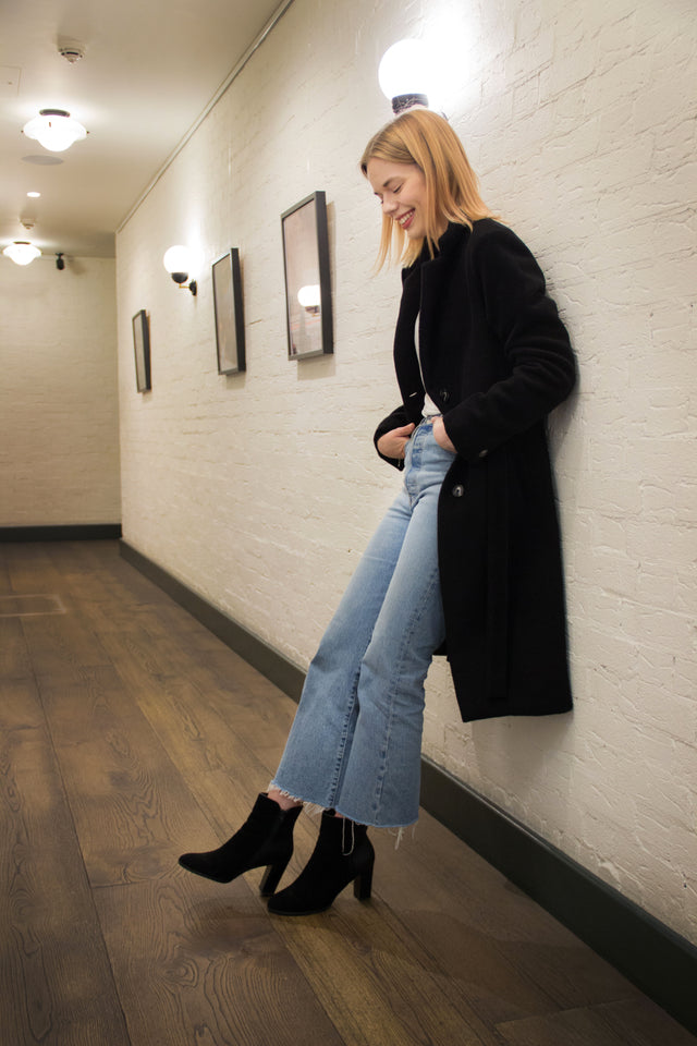 Woman standing in 60s inspired doorway wearing jeans, heels and a black long coat