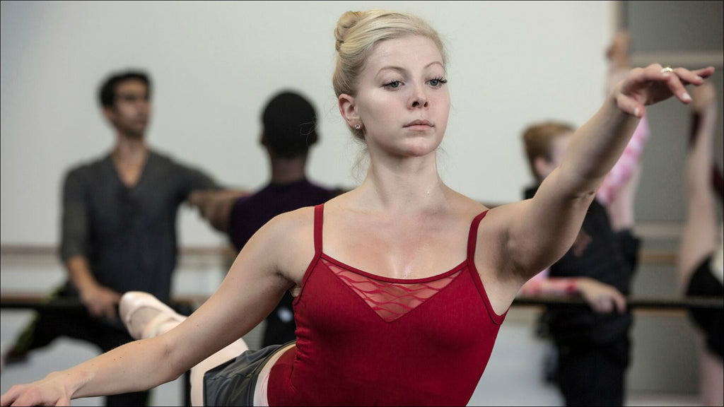 A female dancer practising pointe work at the barre during a ballet class