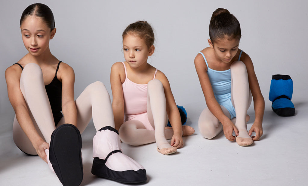 Three young ballet dancers trying on their Warm Up Booties in the studio before class
