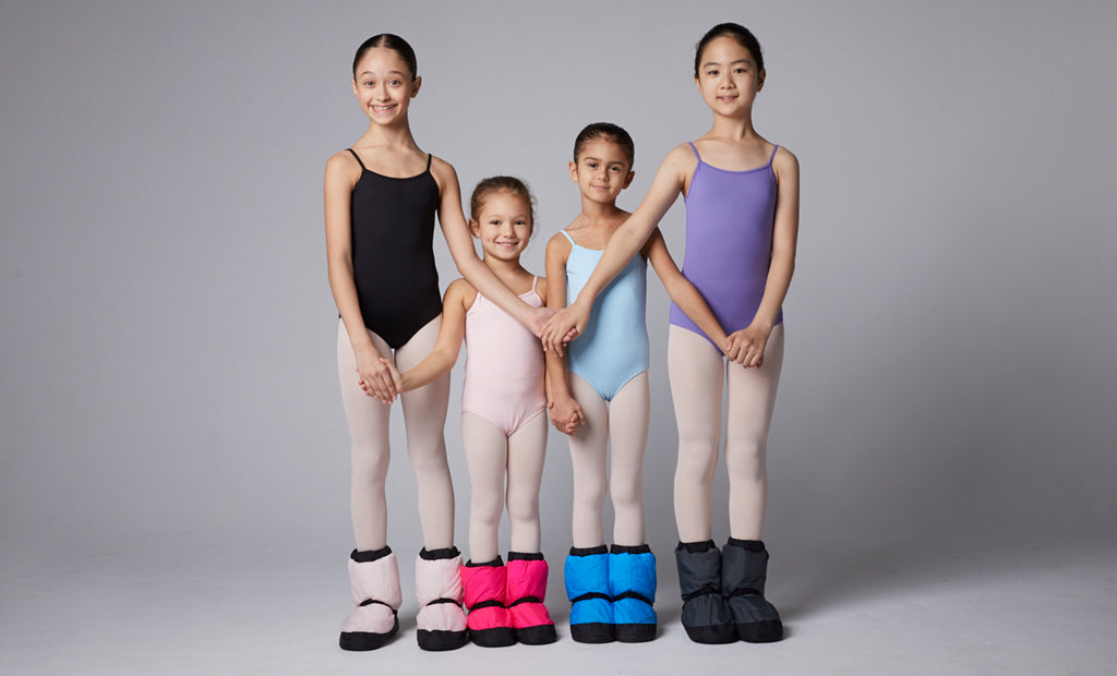 Four young ballet dancers posing together in the studio wearing their Warm Up Booties before ballet class