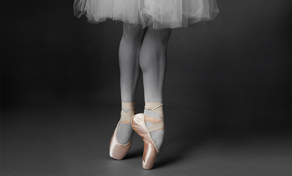 A ballet dancer dancing en pointe in the studio wearing tights, a tutu and Balance Lisse pointe shoes