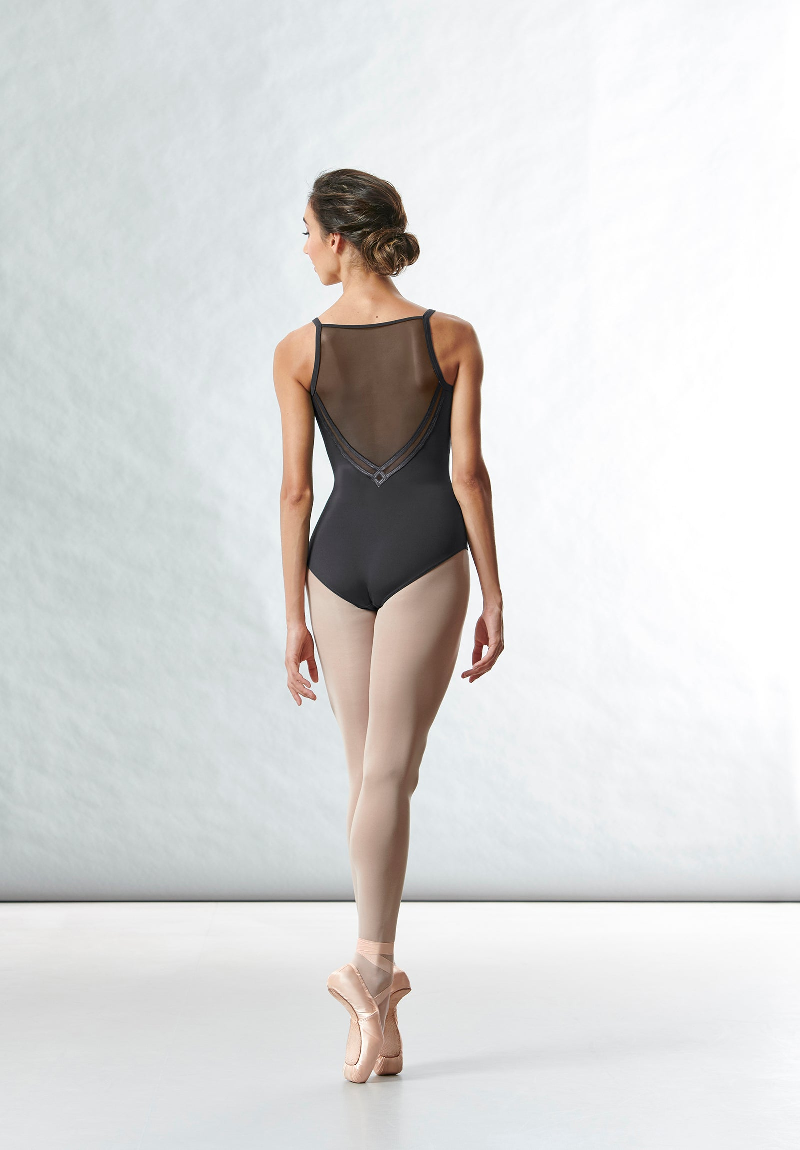 A ballet dancer dancing en pointe wearing the Kora camisole mesh back leotard, pink tights and poine shoes