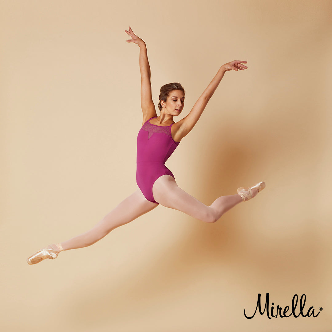 Ballet dancer Sasha Mukhamedov leaping through the air wearing the Mirella open back lace camisole leotard in tulip pink with pink tights and pointe shoes