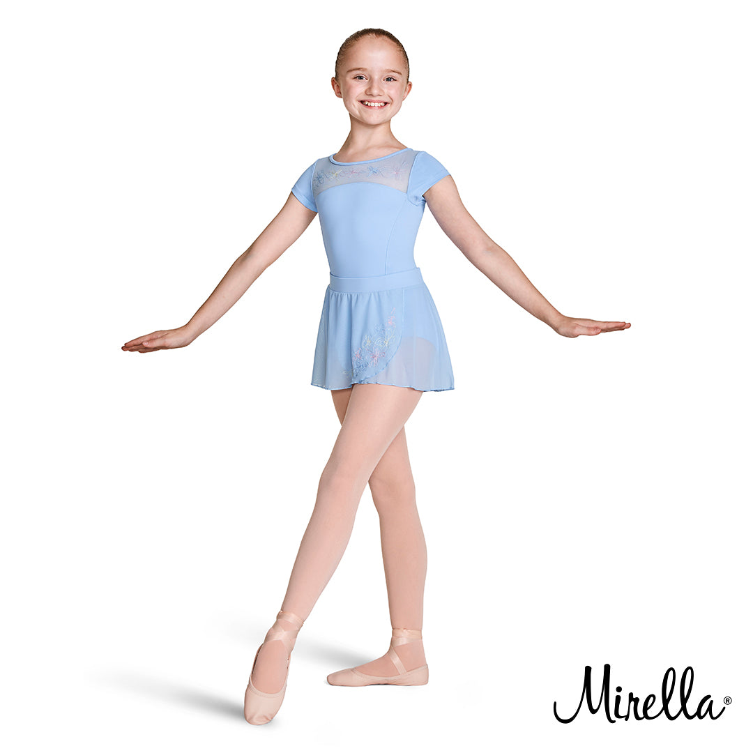 A young female ballet dancer wearing the Mirella embroidered mesh open back leotard and embroidered mesh fixed wrap skirt in blue