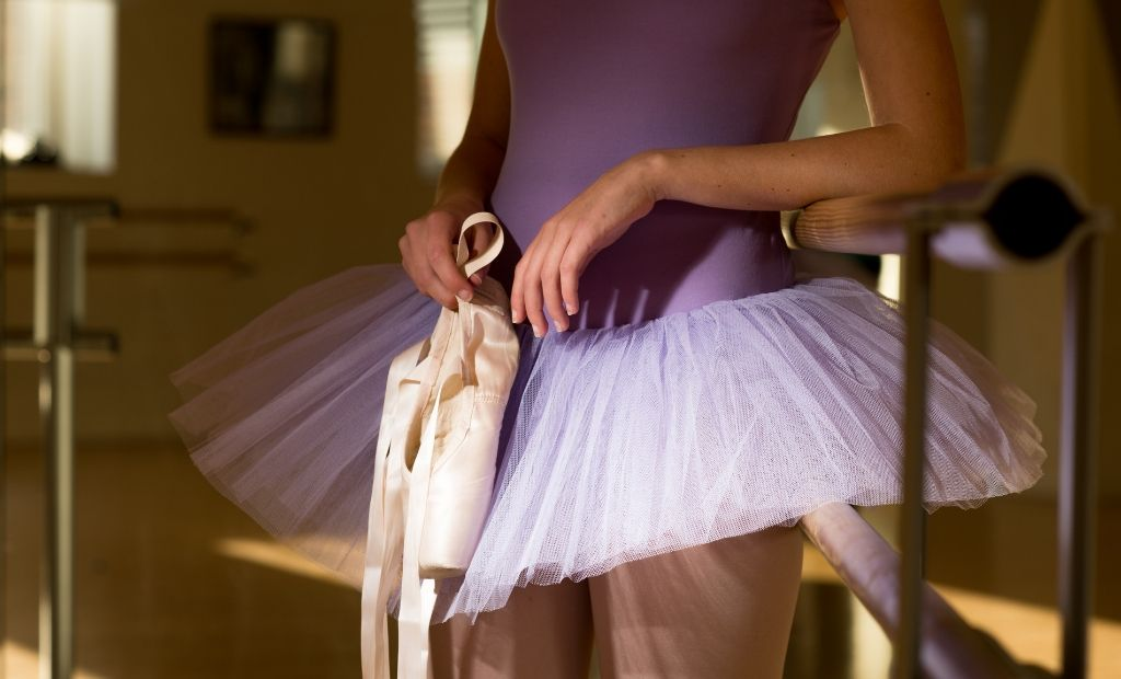 A ballet dancer holding her pointe shoes at the barre
