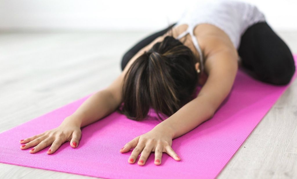 Woman practising the Yoga move known as 'Child's Pose'