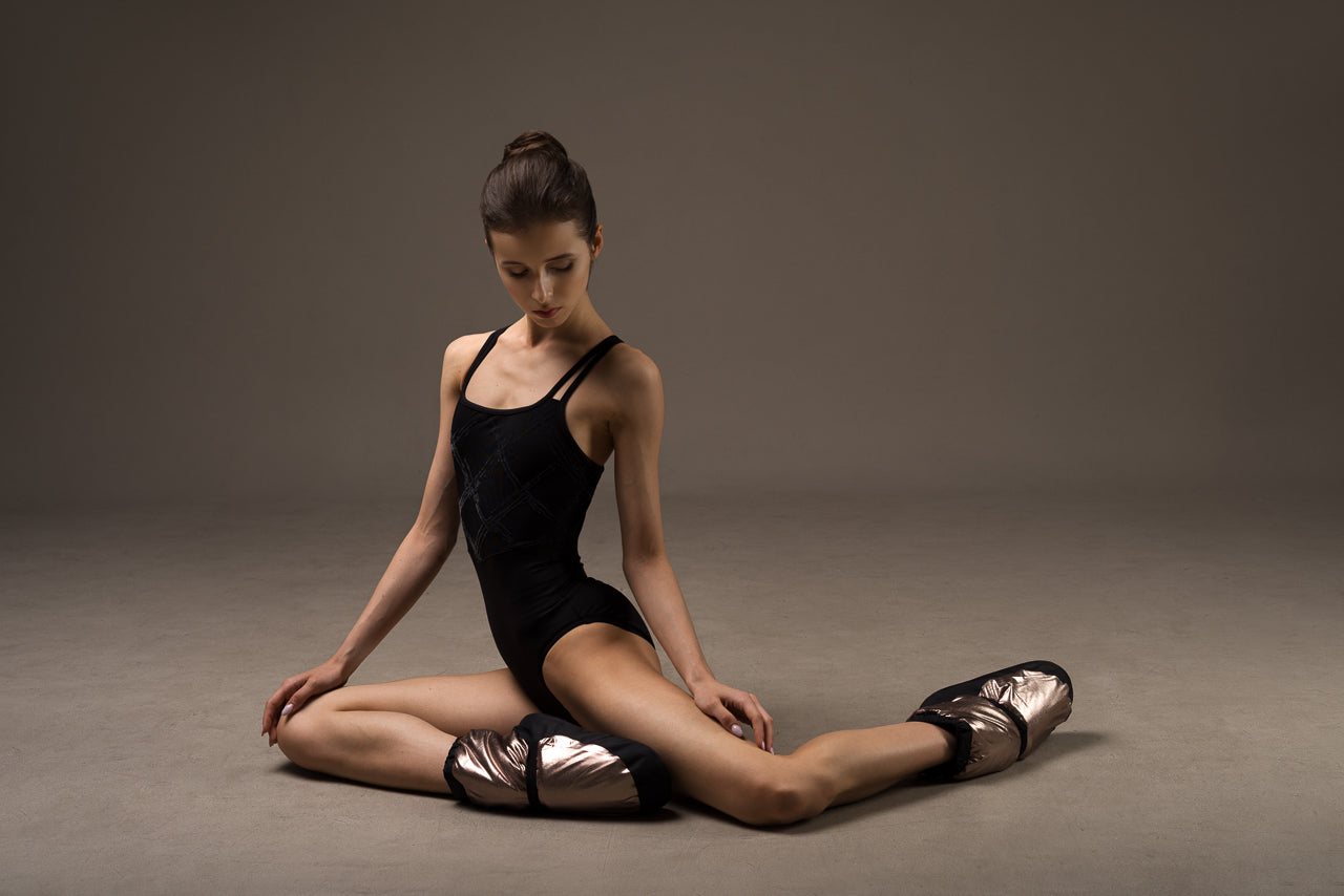 Ballet dancer Maria Khoreva stretching wearing a black BLOCH camisole leotard with Metallic Warm-up Booties
