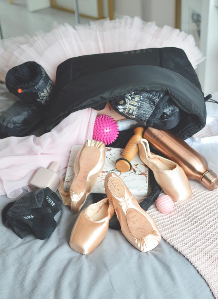 A BLOCH dance bag filled with BLOCH essentials Pointe Shoes, Warm Up Booties, tutu, Foot Roller and water bottle