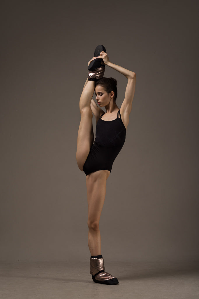 Ballet dancer Maria Khoreva stretching wearing a BLOCH camisole leotard and metallic Warm-up Booties