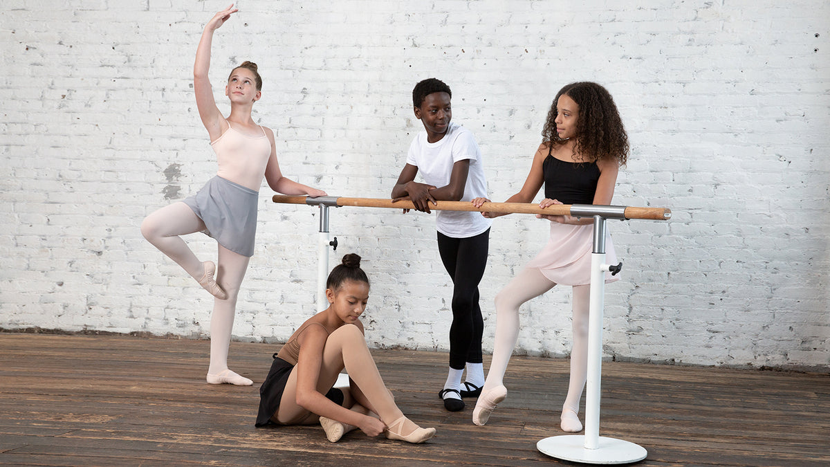 Four young dancers practising at the barre in class