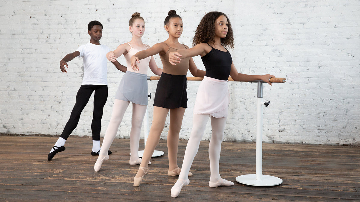 Four young ballet dancers dancing at the barre in class