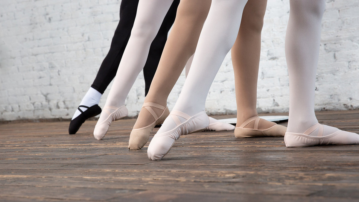 Four young ballet dancers pointing their feet