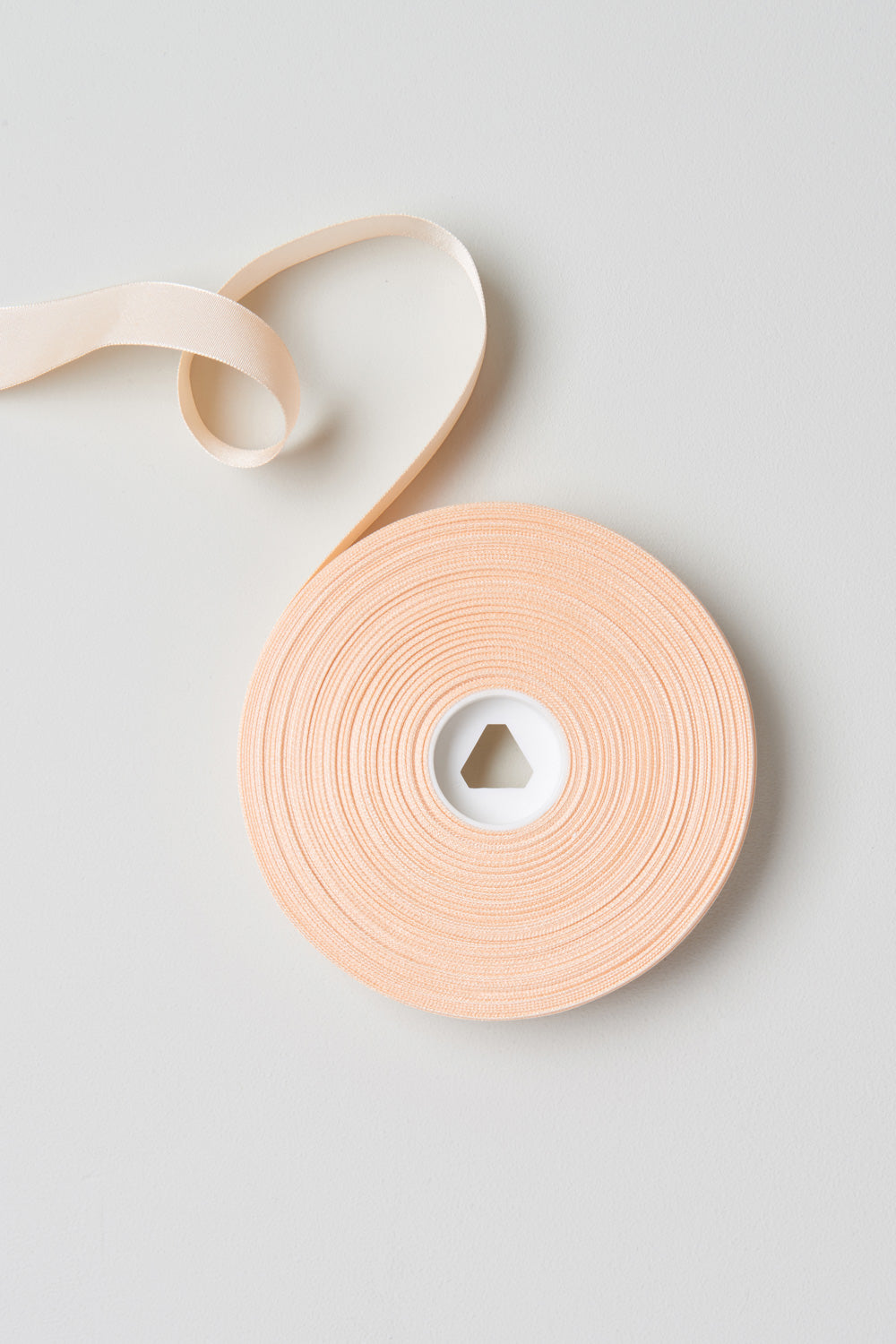 Pink satin Bloch Ribbon Seven Eights Inch flatlay roll of ribbon