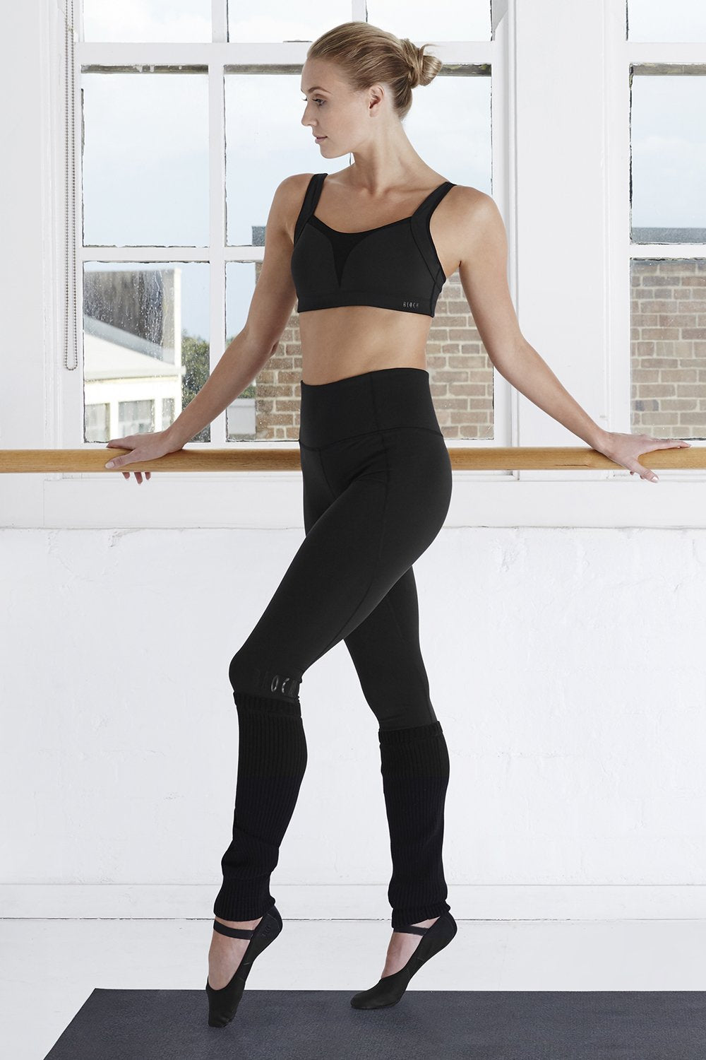 Black Bloch Ladies Legging w Legwarmer on female model with feet in fourth position with arms resting on the ballet barre