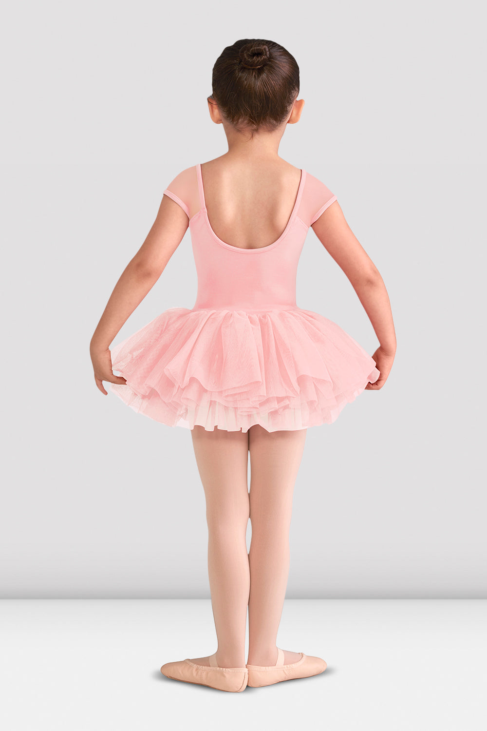 Pink Blossom Bloch Girls Abelle Mesh Tutu Leotard on female model in first position with arms in demi bras facing back