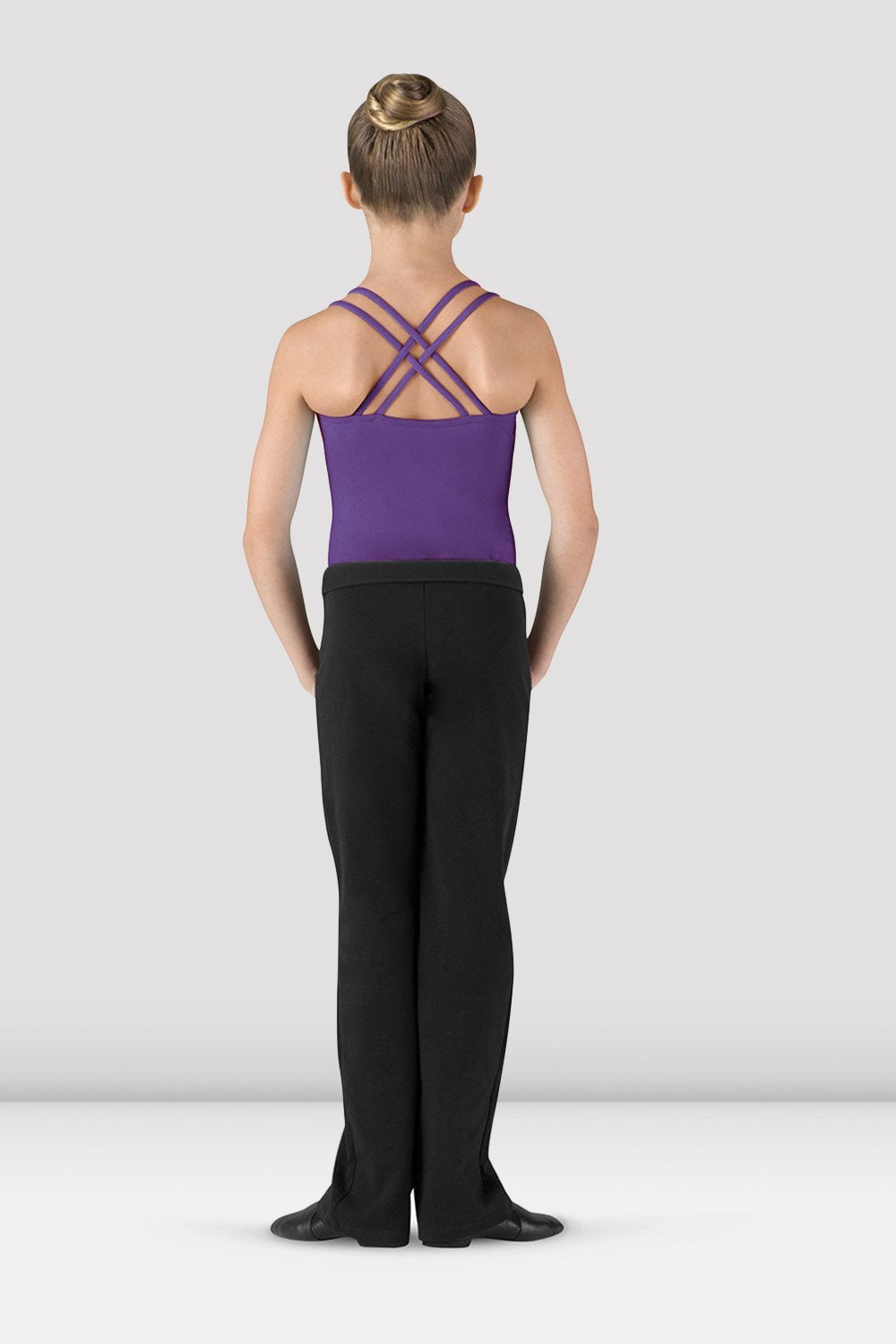 Black Bloch Girls V Front Boot Leg Jazz Pant on female model feet in first position with arms in bra bas facing back