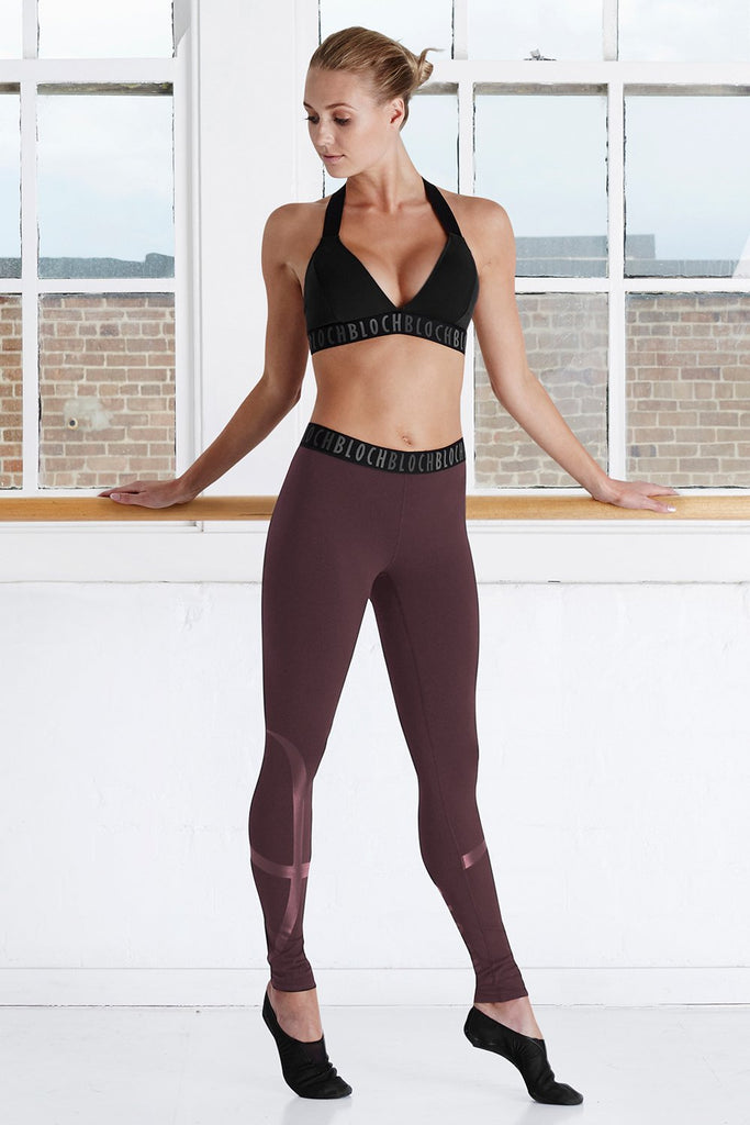 Wine Bloch Ladies Stirrup Legging on female model legs in fourth position hands resting on ballet barre