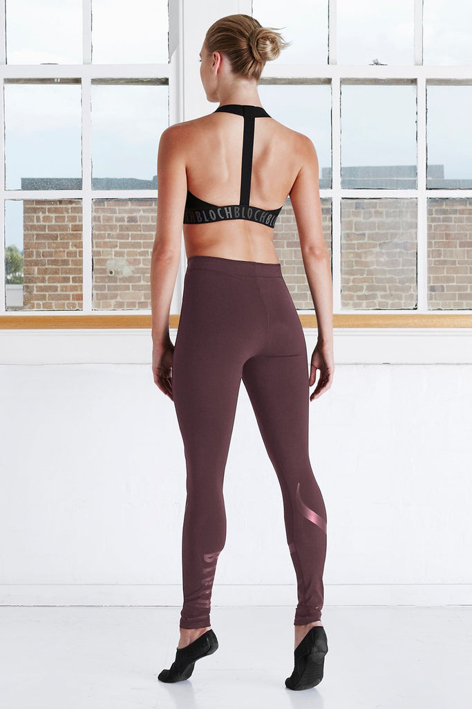Wine Bloch Ladies Stirrup Legging on female model left leg beveled facing upstage right corner