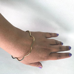 Knuckle Kiss Bloom Bangle in brass, on a wrist