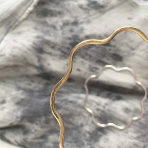 Close up of Knuckle Kiss Bloom Bangle, a flower shaped bracelet in brass