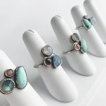 A collection of multi gemstone cluster rings by Knuckle Kiss Jewelry