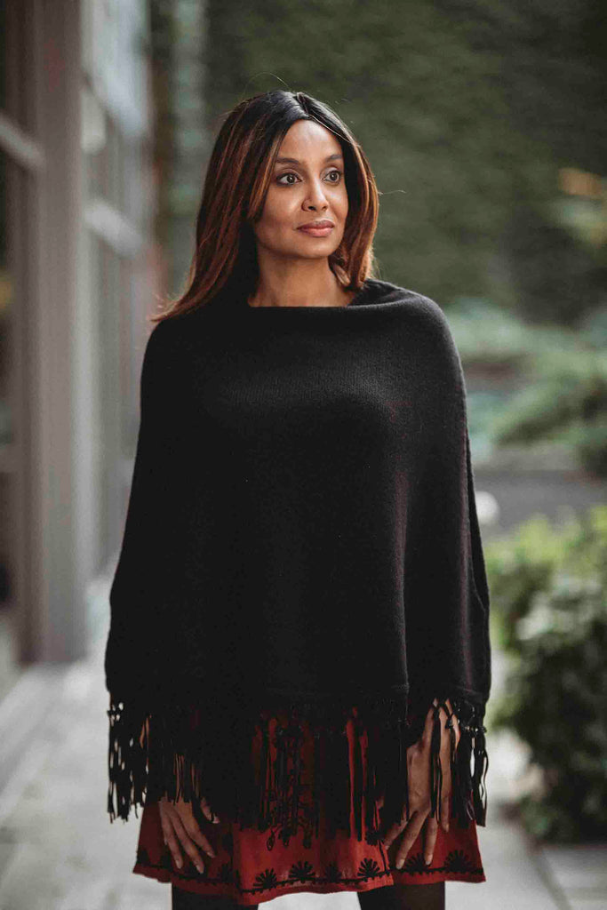 Woman wearing black cashmere and suede poncho over a red and black mini dress