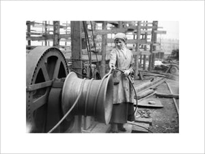 A female worker operates a winch at a shipbuilding yard on the River Clyde in Scotland during the First World War.