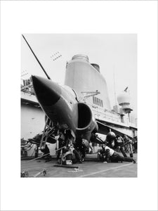 Armourers 'bombing up' a Sea Harrier on board HMS INVINCIBLE during the Falklands War, 1982.