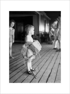 A small child on deck with his life belt on board SS EMPRESS OF AUSTRALIA, August 1941.