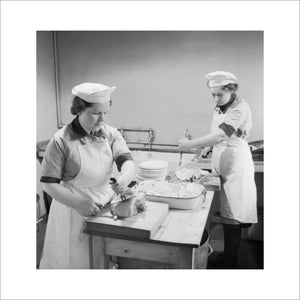 Two Wren cooks carve ham for the lunchtime meal in the galley of a Fleet Air Arm base in Scotland, 1943.