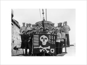 "The crew of HM Submarine UTMOST displaying their ""Jolly Roger"" at Holy Loch in Scotland after a successful year's service in the Mediterranean, 6 February 1942."