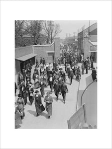 Workers at the Royal Arsenal, Woolwich, London, leave from the Fourth Gate, by Plumstead station, May 1918.