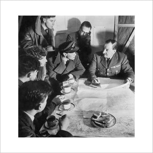 Cecil Beaton photograph of an RAF bomber crew being debriefed by the squadron intelligence officer on their return from a night raid over Germany, 1941.