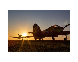 Two Hawker Hurricanes at the Duxford Airfield during sunrise