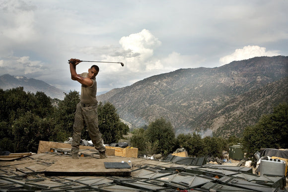 Soldier practices his golf swing at the main Korengal Outpost (KOP), Afghanistan. 2008.
