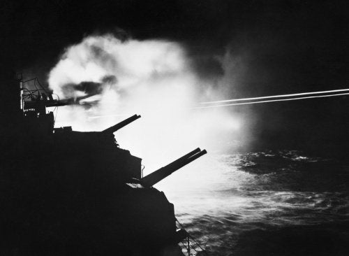 HMS MAURITIUS firing during a night action against enemy ships off the French coast between Brest and Lorient, 23 August 1944.