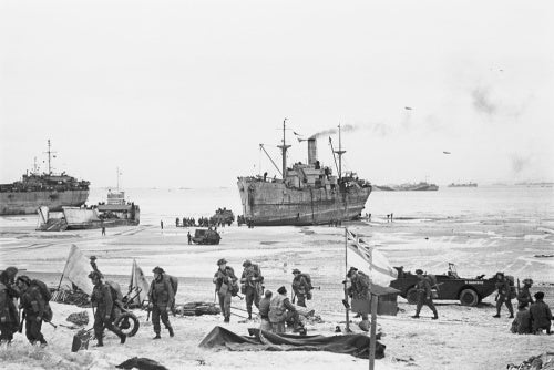 Troops come ashore on one of the Normandy invasion beaches, past the White Ensign of a naval beach party, 7 June 1944.