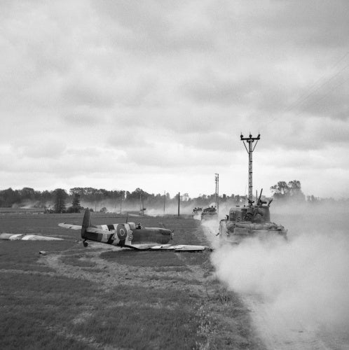Sherman tanks move up past a crash-landed Spitfire, for an attack on Tilly-sur-Seulles, Normandy, 17 June 1944.