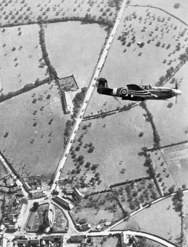 A North American Mustang  Mk I of No. 168 Squadron banking over Pierrefitte-en-Cinglais in Normandy on a tactical reconnaissance sortie, August 1944. Allied tanks can be seen on the road below.