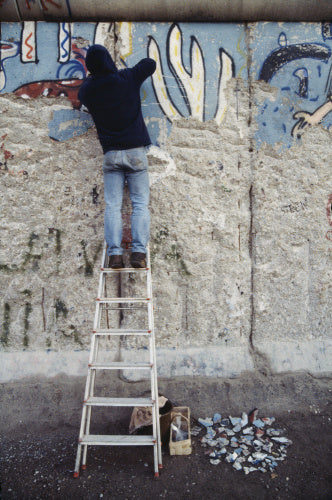 A Berliner chipping away part of the newly-opened Berlin Wall, 23 January 1990