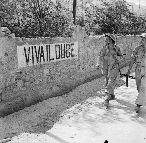 British soldiers smile at a 'Viva Il Duce' slogan on a wall in Reggio, Italy, September 1943.