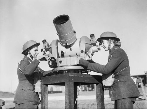 Two members of the Auxiliary Territorial Service (ATS) check the accuracy of anti-aircraft fire from a gun battery during the Second World War.