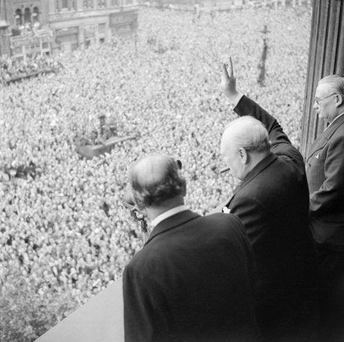 Winston Churchill waves to crowds in Whitehall in London as they celebrate VE Day, 8 May 1945.