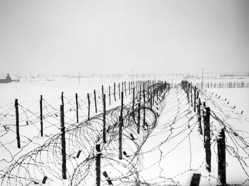 Lines of barbed-wire obstacles stretch across snow-covered fields near Menin in France, 21 January 1940.