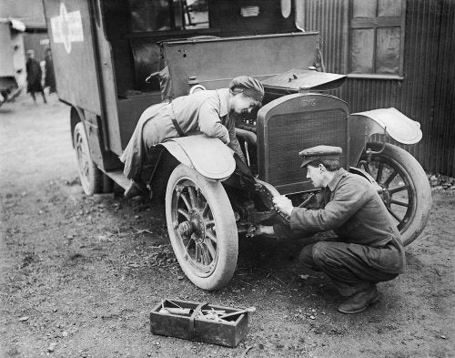 An ambulance driver of the First Aid Nursing Yeomanry (FANY) assists with the maintenance of her vehicle at St Omer, 28 February 1917.