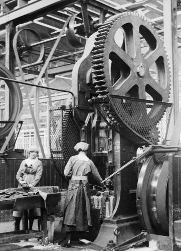 Two women munition workers operate a shell case forming machine during the First World War at the New Gun Factory of the Royal Arsenal, Woolwich, London.