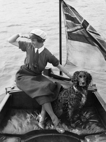 Gladys Wilburn, a motor boat driver with the Women's Royal Naval Service, in her boat, the 'BALMACAAN', with her spaniel dog, Southwick, Sussex, 1918.